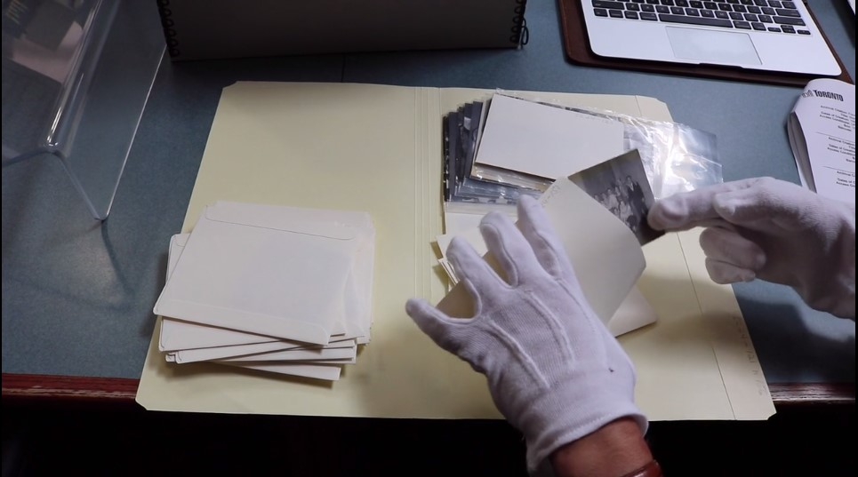Photograph of gloved hands handling archival photographs