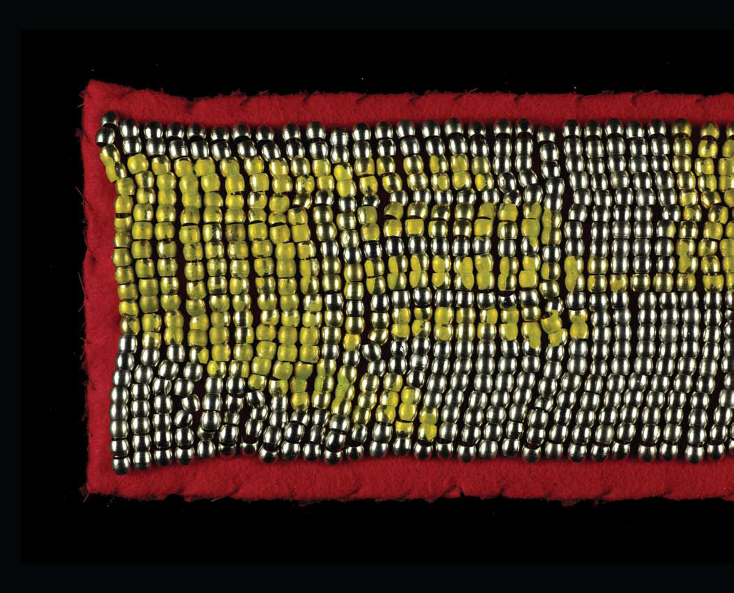 Photograph of woven grid of white, yellow and red beads against black background